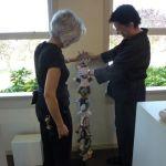 Gabriella assisitng Marcia set up a hanging piece.